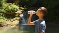 Boy drinks water from bottle near waterfall 42997468