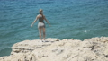 Young girl stands on ruined stone wall and looking at the sea 43012252