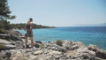 Young girl stands on ruined stone wall and looking at the sea 43012255
