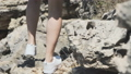 Close-up girl's lags walk on stone cliff at sea. FullHD 43012264