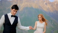 Loving newlyweds walking in a meadow against the backdrop of beautiful mountains 43588900