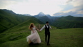 Enamored newlyweds walk in the evening in the meadow against the backdrop of beautiful mountains 43589261