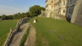 Aerial view of wedding couple walks and poses at ancient castle background 43767748