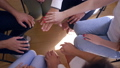 team spirit, young people making stack of hands moving up and down sitting in circle on group 43874604