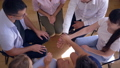 group therapy, women and men stack hands as symbol for support sitting in circle on chairs 43874628