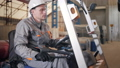 man driving a forklift through a warehouse in a factory. driver in uniform and protective helmet 44322398
