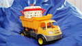 toy tipper truck with pan in workbody stands on blue bag chair 44331481