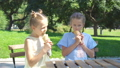 Little girls eating ice-cream outdoors at summer in outdoor cafe 44337643
