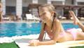 Beautiful little girl having fun near an outdoor pool 44337644