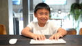 Asian boy using computer and presses on the keys 44355015