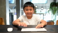 Asian boy learns the computer presses on the keys  44355016