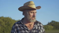Portrait of senior farmer looking on the harvest and bright sky 44409113