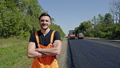 Man in overalls standing alongside a tarred road 44412086