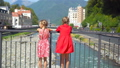 Back view of girls on the embankment of a mountain river in a European city. 44415744