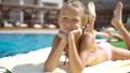 Beautiful little girl having fun near an outdoor pool 44415745