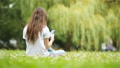Cute woman is reading text message on mobile phone while sitting in the park. 44415752