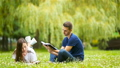Relaxed young couple reading books while lying on grass 44415754