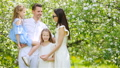 Family of four in blooming garden on beautiful spring day 44415758