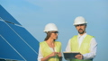 Solar engineers talk while walking on a roof with a tablet. 44485809