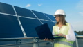 An engineer types on a laptop while checking solar batteries. FullHD. 44485816