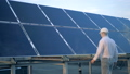 A man checking solar panels. An engineers looks at sun batteries and touches them. 44485818