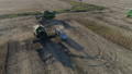combine harvester pours soy into truck body while harvesting legumes in the sunlight, drone view of 44505874