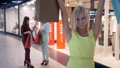 portrait of happy shopping girl in yellow dress with paper bags stands on background of two girls 44505900