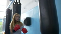 young sportswoman wearing gloves in boxing hall beating a punching bag 44505901