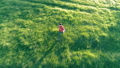 Flight over sporty man running at perfect green grass rural meadow offroad. Sunset in mountain 44582910