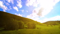 Mountain meadow timelapse at the summer. Clouds, trees, green grass and sun rays movement. 44582937
