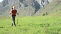 Hiking man walking on green mountain meadow with backpack. Summer sport and recreation concept. 44582949