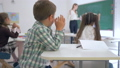 upset schoolboy sits at a desk in classroom on background of classmates and female teacher near 44989087