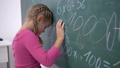 unhappy schoolgirl near board with examples on mathematics in elementary school class 44989088