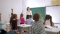 teacher stands at front of class near blackboard and asks pupils question to which they raise their 44989090