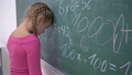 schooling, female pupil tired of studies standing near blackboard with mathematics examples 44989092