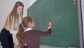schoolgirl with piece of chalk writes an example on the blackboard with help of a female teacher at 44989096