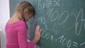 school education, upset female pupil standing near blackboard with mathematics examples 44989098