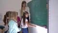 pupils and teacher standing near whiteboard in classroom, schoolgirl takes piece of chalk and writes 44989100