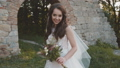 Happy bride with bouquet in hands smiles and poses at ancient castle 45006615
