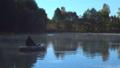 A fisherman on the boat at foggy lake 45100315