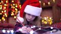 Funny girl in Santa hat writes letter to Santa 45278662