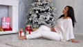 happy pregnant mom by the Christmas tree with Christmas gifts 45308438