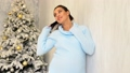 happy pregnant mom by the Christmas tree with Christmas gifts 45308439