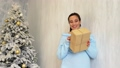 pregnant mom stands by the Christmas tree with White Christmas gifts 45308841