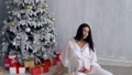 pregnant mom at Christmas tree looking Christmas gifts 45308848