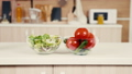 Tow glass bowls with salad, tomatoes and cucumbers on the kitchen table 45814919