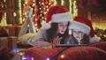 mother and daughter lying on the bed and watch the tablet in the Christmas decorations 45853003