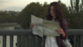 Beautiful young woman with tourist map looking aroung in the city street. 45871758