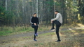 Bearded young man is doing sports in park with his girlfriend stretching legs doing warm-up smiling 45893260
