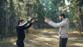 Young couple man and woman are doing sports outdoors in park twirling arms and smiling enjoying warm 45893276